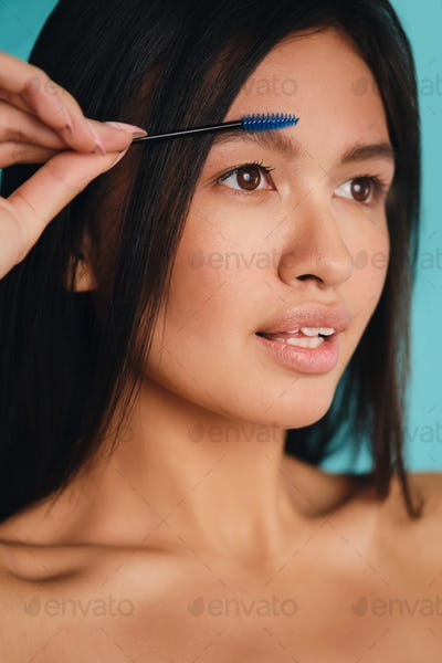 Beautiful Asian brunette girl with cosmetic brush applying eyebrow gel over colorful background