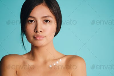Beautiful Asian brunette girl with points of cream on clavicle intently looking in camera