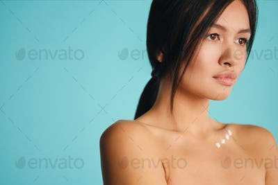 Attractive Asian brunette girl with points of cream on clavicle sensually