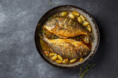 Baked sea bream or dorada with onion and herbs in pan on dark background.