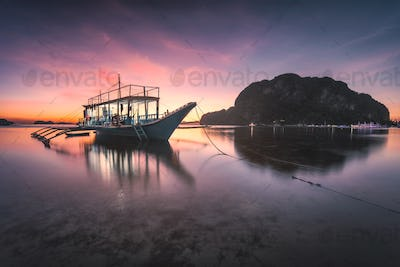 Banca boat at Corong Corong beach on low tide shallow water in twilight lit by sunset light, El Nido