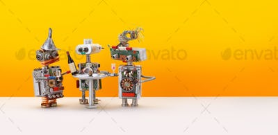 Robotic drink party. Three toy robots celebrate new system update. Yellow background, copy space