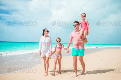 Happy family with kids walk on the beach