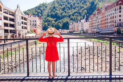 Little girl at hat on the embankment of a mountain river in a European city