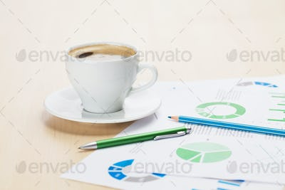 Office workplace with coffee cup and charts