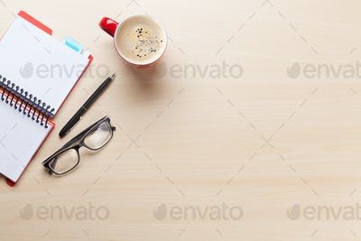 Office desk with coffee cup, notepad and glasses
