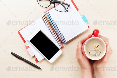 Woman holding coffee cup on business desk