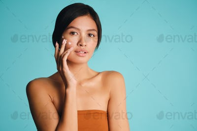Attractive Asian brunette girl with points of cream on cheek posing over colorful background