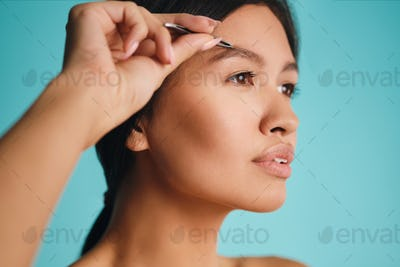 Side view of beautiful Asian brunette woman dreamily plucking eyebrows over colorful background