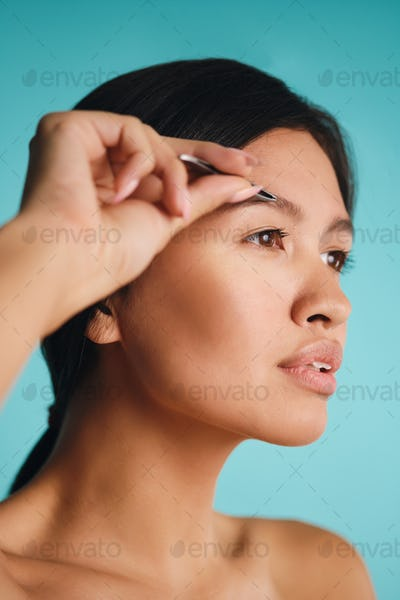 Portrait of attractive Asian brunette woman plucking eyebrows over colorful background