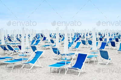 Beach umbrellas and blue deckchairs