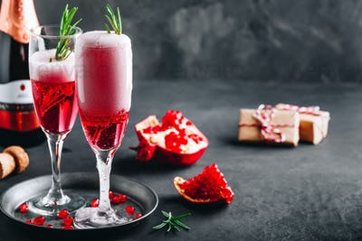Pomegranate Champagne Cocktail with rosemary on gray concrete stone background