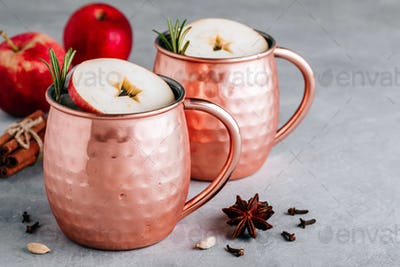Apple Cider Moscow Mule cocktail with cinnamon stick and rosemary in copper