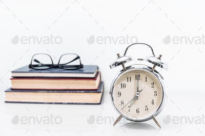 Alarm clock with old book with eyeglasses-2