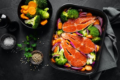 Salmon. Cooking fresh raw salmon fish steaks with vegetables, broccoli, carrot and onion