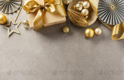 Gift box with golden ribbon on grey background