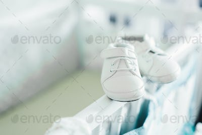 Baby shoes on baby bed