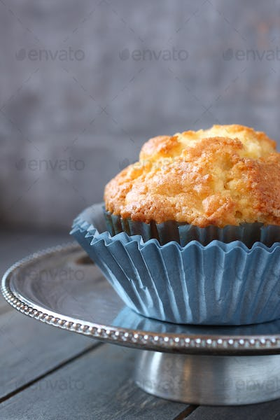 Muffin with raisins in blue wrappers on a metal plate