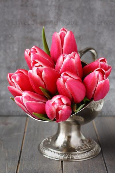 Bouquet of pink tulips in metal vase on wooden background