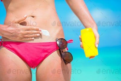 Woman hand putting sunscreen from a suncream bottle