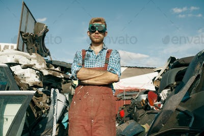 Dirty repairman in welding glasses on car junkyard