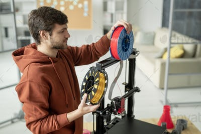 Young creative man changing spool with filament while standing by 3d printer