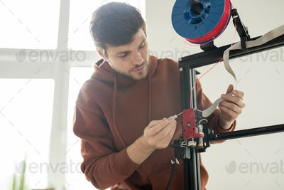 Young engineer with screwdriver repairing printhead of 3d printer