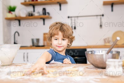 Cute little boy in apron stretching hand to one of raw cookies on table