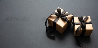 Gifts with black ribbon against black background, Black Friday concept.
