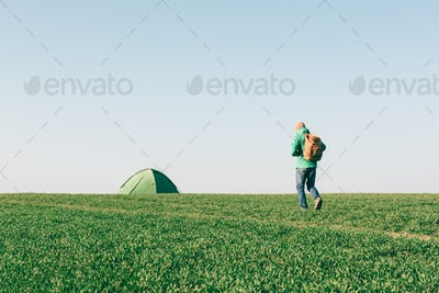 Tourist with backpack going to his tent