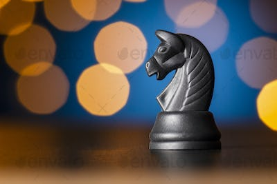 black horse chess piece over a colorful bokeh