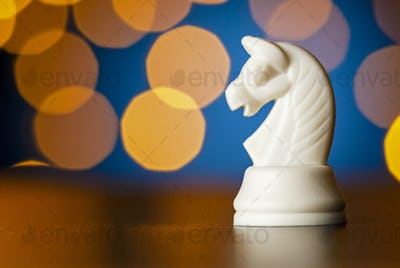 White horse chess piece over a colorful bokeh