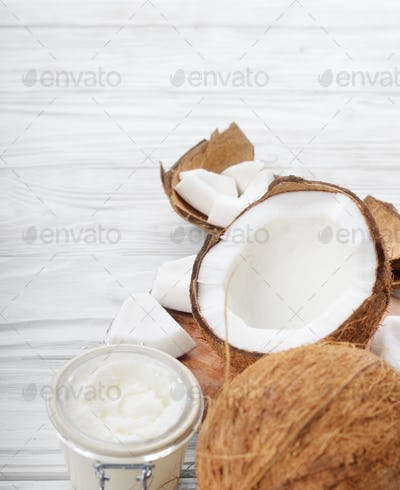 Coconut oil in airtight glass jar and shell pieces on white wood
