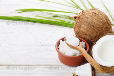 Background of coconut, coconut shell, oil in clay bowl and spoon