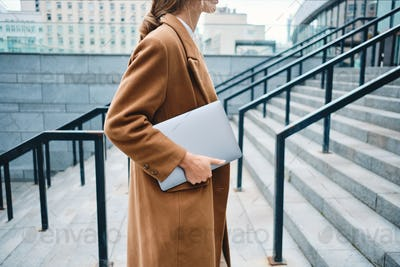 Close up stylish businesswoman in coat with laptop on city street