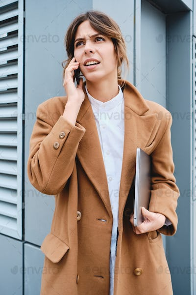 Young dissatisfied businesswoman in coat with laptop angrily talking on cellphone outdoor