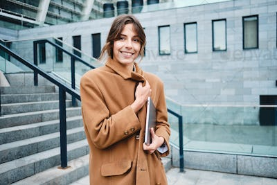 Young attractive stylish businesswoman in coat with laptop dreamily looking away outdoor