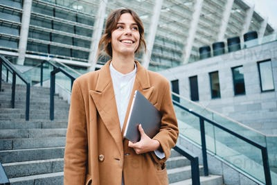 Young pretty positive businesswoman in coat with laptop joyfully looking away outdoor