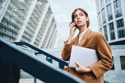 Pensive businesswoman in coat with laptop talking on cellphone thoughtfully looking away outdoor