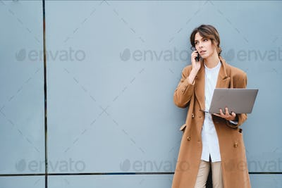 Young attractive businesswoman in coat with laptop thoughtfully talking on cellphone outdoor