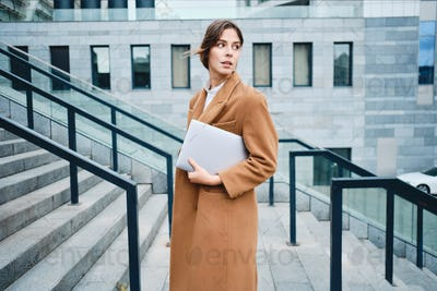 Young beautiful businesswoman in coat with laptop thoughtfully looking away outdoor