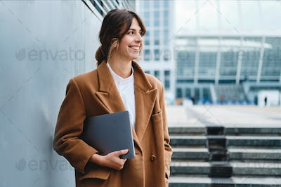 Young cheerful businesswoman in coat with laptop happily looking away on city street