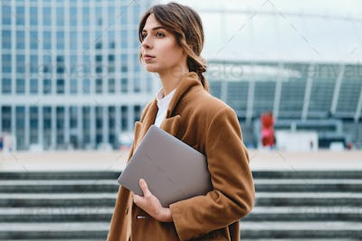 Young beautiful businesswoman in coat with laptop intently looking away on city street