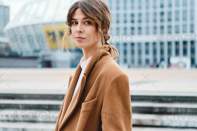 Young stylish woman in coat confidently looking in camera on city street