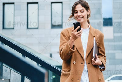 Young pretty casual businesswoman in coat with laptop joyfully using cellphone outdoor