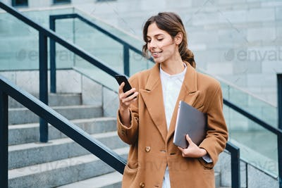 Young smiling casual businesswoman in coat with laptop happily using cellphone outdoor