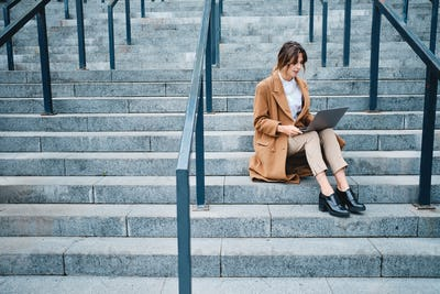Young attractive businesswoman in coat confidently working on laptop on stairs outdoor