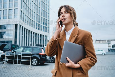 Young attractive businesswoman in coat with laptop thoughtfully talking on cellphone on city street