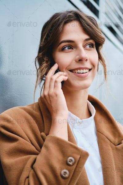 Young beautiful stylish businesswoman in coat happily looking away talking on cellphone outdoor