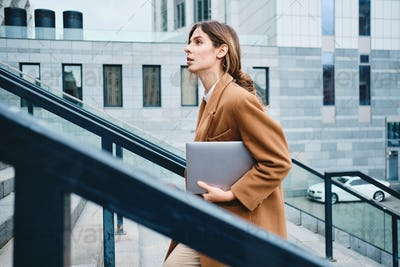 Side view of young gorgeous businesswoman in coat with laptop going up the stairs outdoor